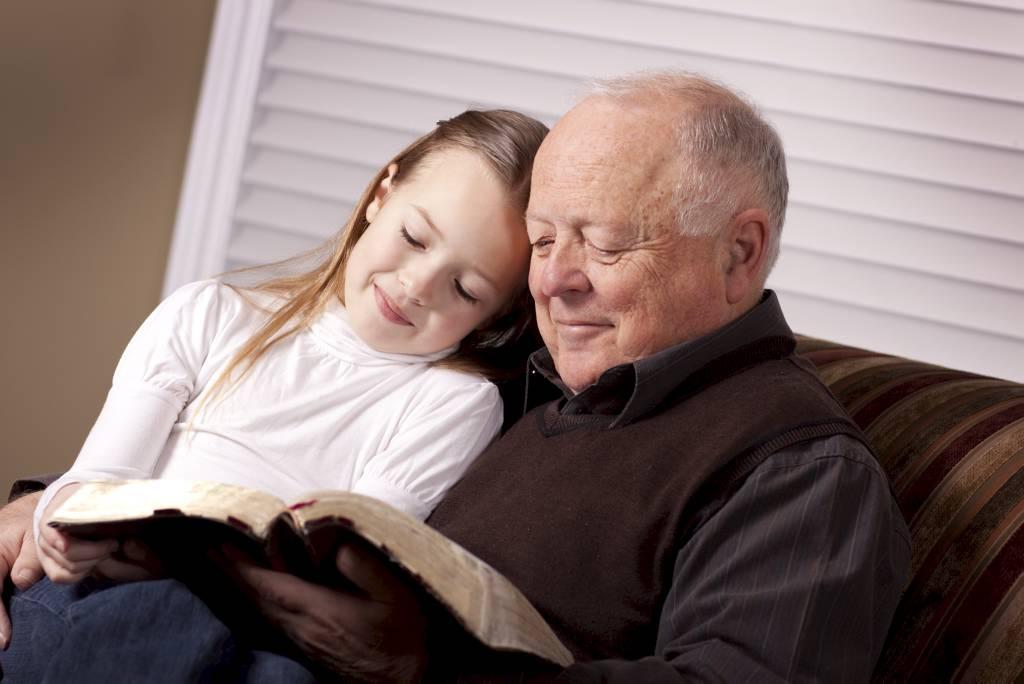 Een opa leest voor aan zijn kleindochter of kleinkind
