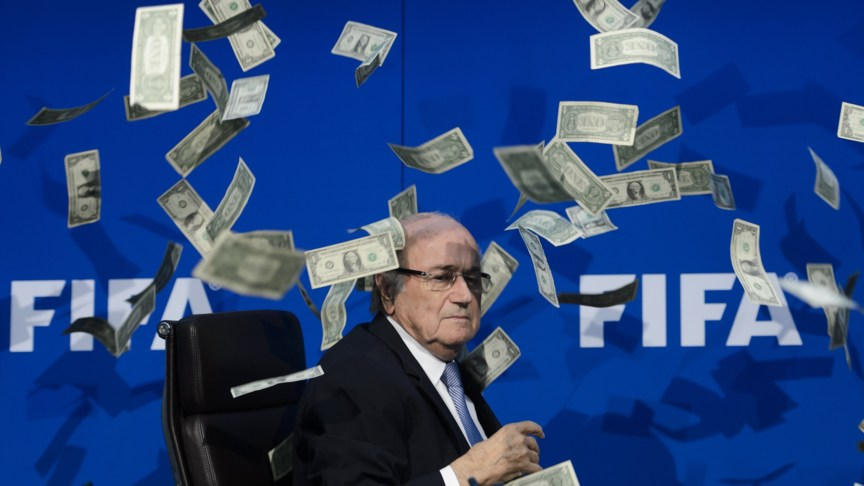 FIFA president Sepp Blatter looks on with fake dollars note flying around him throw by a protester during a press conference at the football's world body headquarter's on July 20, 2015 in Zurich. FIFA said Monday that a special election will be held on February 26 to replace president Sepp Blatter. AFP PHOTO / FABRICE COFFRINI