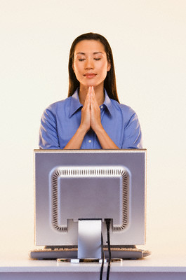 Businesswoman praying in front of computer --- Image by © Don Mason/Blend Images/Corbis